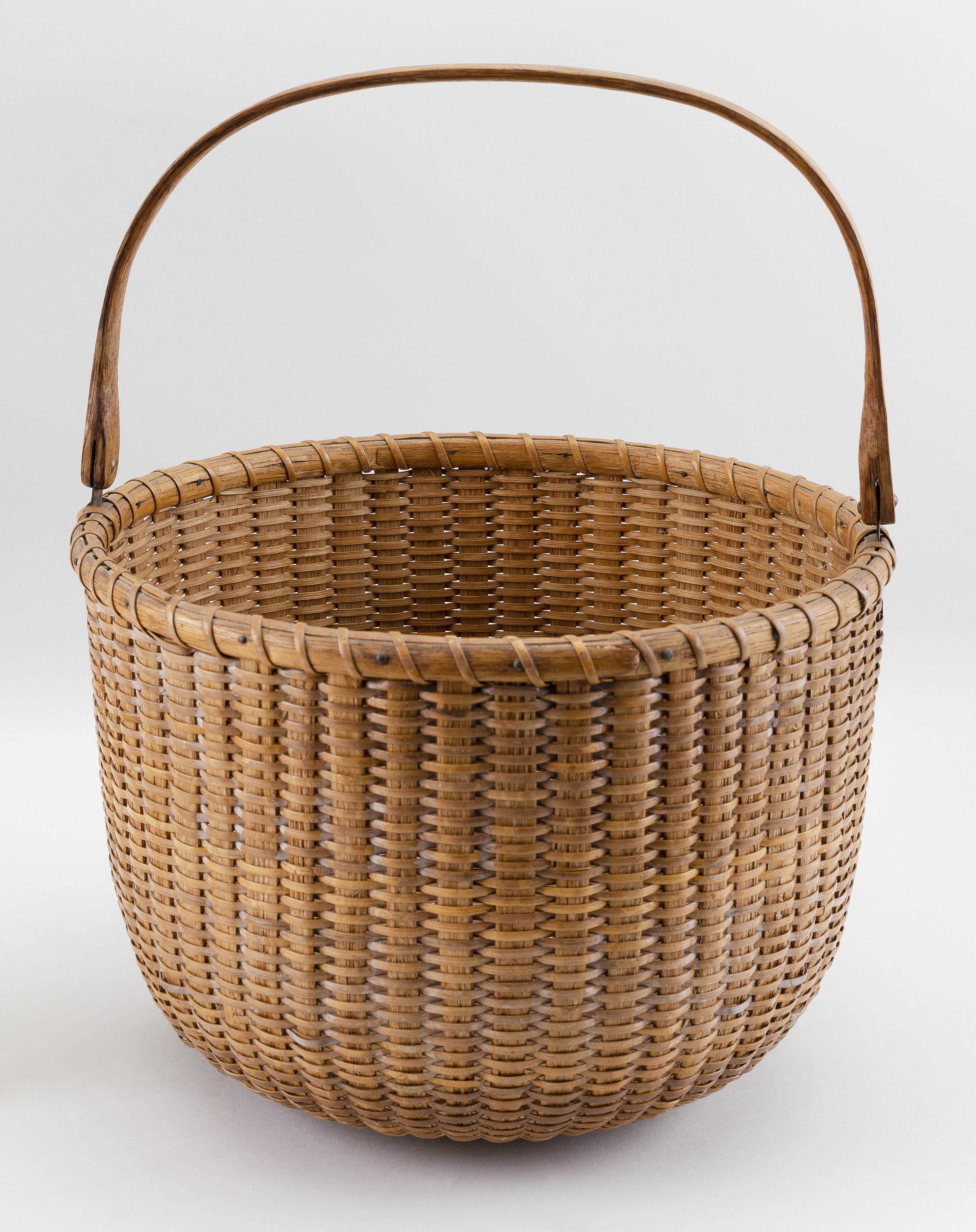 """ROUND NANTUCKET BASKET WITH SWING HANDLE 20th Century Diameter 10.5"""". Height 7.5"""" (not including handle)."""